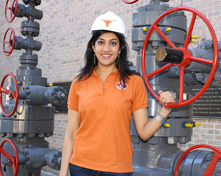 Sharma poses by pressure valves in a hardhat emblazoned with UT logo.