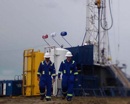 Two men in blue jumpsuits walk in front of an oil derrick.