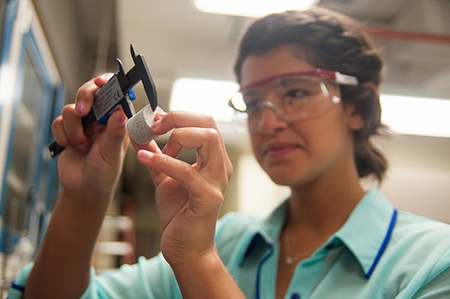 A student in safety goggles working with lab equipment.