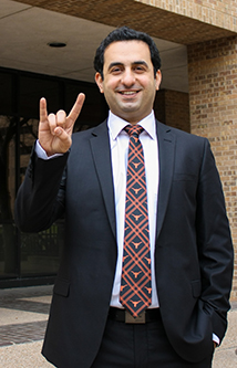 Eshkalak poses in a suit doing the hook 'em horns sign.
