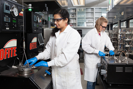Two women in lab coats and safety equipment work in a lab.