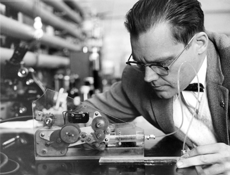 Black and white photo of a man tinkering with a small machine.
