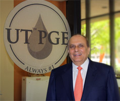 S. Javaid Anwar posing in front of poster with PGE logo.